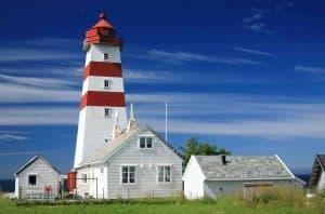 Roter und weißer Leuchtturm von Alnes unter blauem Himmel
