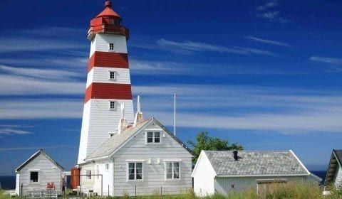 Red and white lighthouse of Alnes under a blue sky