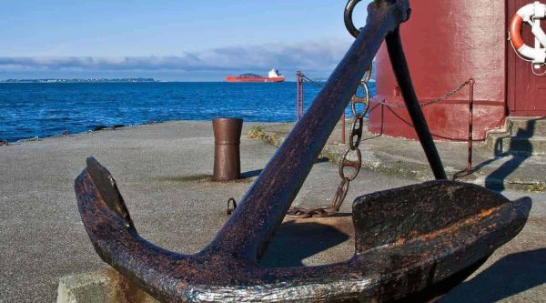 Massive anchor on a small pier in front of a red lighthouse in the center of Ålesund