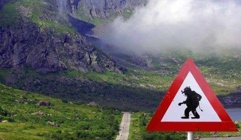Señal de advertencia de los troles en un valle verde entre Ålesund y Åndalsnes, Noruega