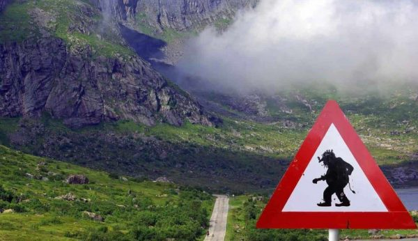 Sign warning for crossing Trolls in a green valley between Ålesund and Åndalsnes, Norway