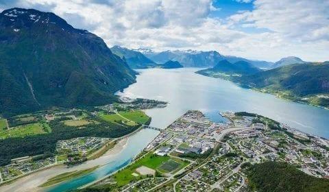 Vue panoramique sur la ville d'Åndalsnes, la rivière Rauma bleu clair et le Romsdalsfjord, entourés de hautes montagnes