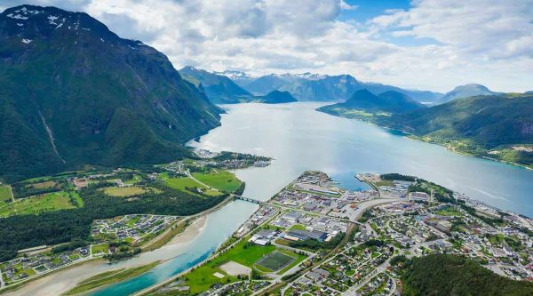 Panoramic view over the city of Åndalsnes, the clear blue Rauma river and the Romsdalsfjord, surrounded by high mountains