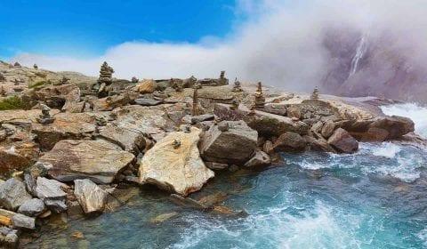 Ometti di pietra, pietre e rocce lungo l'acqua alla cima della cascata Stigfossen e la Strada dei Troll in Norvegia