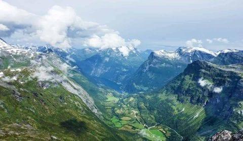 11Panoramautsikt fra Dalsnibba over den grønne dalen, Geiranger og Geirangerfjorden, snø på fjellene og skyer som nærmer seg