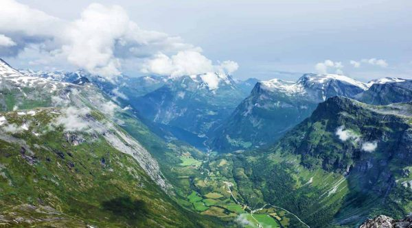 Panoramic view from Mount Dalsnibba over the green valley, Geiranger and the Geirangerfjord, snow on the mountains and clouds approaching