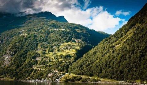 Vista hacia el zigzag de la carretera del Águila subiendo a las montañas en Geiranger, Noruega