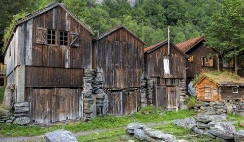 Viejas cabañas de madera a la orilla del camino en las montañas hacia la granja de cabras Herdal en Geiranger