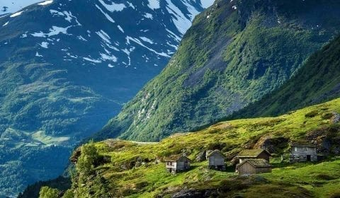 Wooden cabins with grass rooftops in the high mountains, snow on the mountain peaks