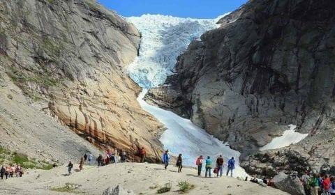 11Toeristen bezoeken de Briksdal Gletsjer, een gletsjer arm op de hoge bergen onder een helder blauwe lucht