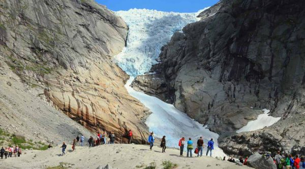 Tourists visiting the Briksdal glacier, glacier arm on the high mountains under a clear blue sjy