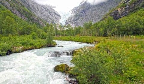 11Water stromend van de Briksdal Gletsjer door de groene vallei omringd door hoge bergen