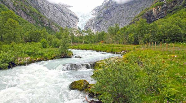 Water streaming from the Briksdal glacier through the green valley surrounded by high mountains