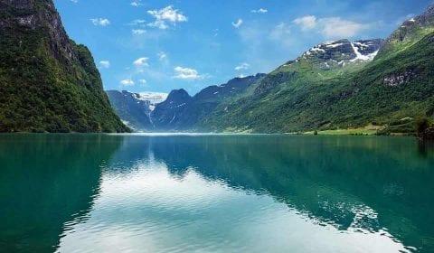 11Turquoise water in het meer Oldevatnet, omringd door groene bergen op een heldere dag, de Melkevoll Gletsjer op de bergen in de achtergrond