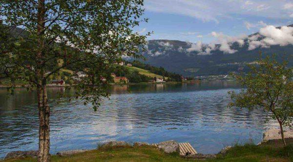 Vista pittoresca dalla riva verso un fiordo calmo, circondato da montagne alte