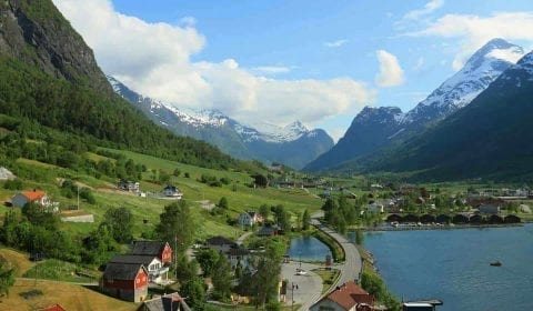 Vue sur le village d'Olden dans une vallée verte entre les montagnes