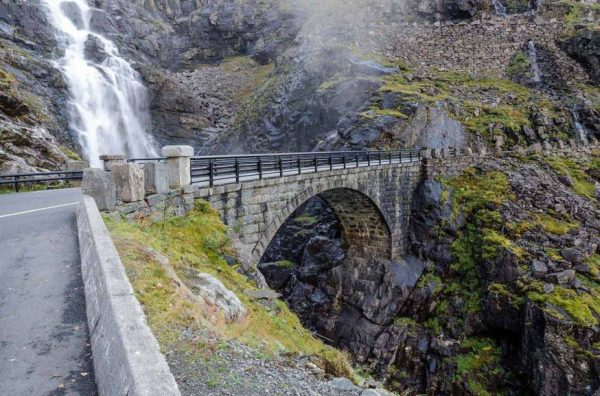 Stone bridge crossing spectacular waterfall, steep mountain road with hairpin bends, green grass on mountain sides