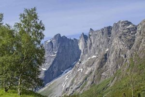 Europe's tallest vertical rock face, the Troll Wall, with rugged peaks under a blue sky