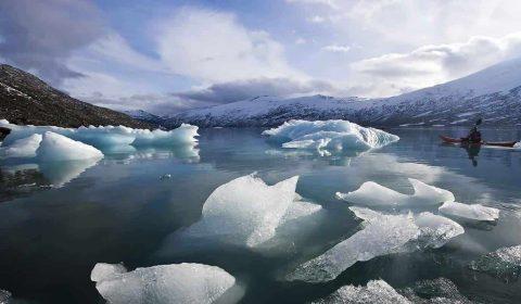 Canoista in un kayak sul lago di un ghiacciaio, pezzi di giacchio sulla riva
