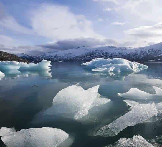 Kayakista en un lago glaciar, bloques de hielo flotando en el agua