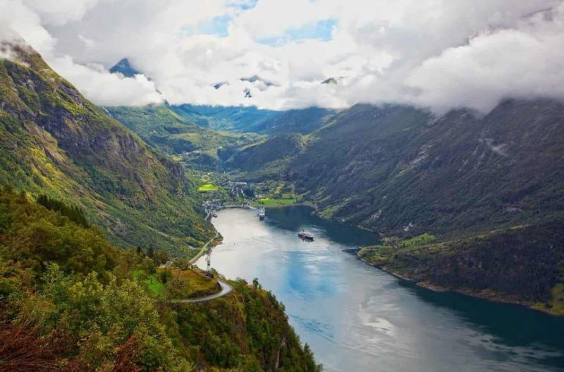 Two cruise ships in fjord, small village, steep mountainsides covered with green trees, mountain peaks in clouds