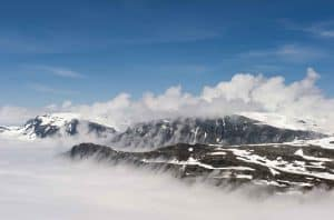 View from Mount Dalsnibba over Lake Djupvatn covered under the clouds, mountain peaks with snow stick out above the clouds