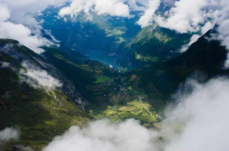 View over the Geirangerfjord, the Eagle Road, green mountains with peaks covered by clouds