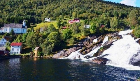 Hellesylt waterfall streaming from the mountain in the fjord, houses and church on the mountainside