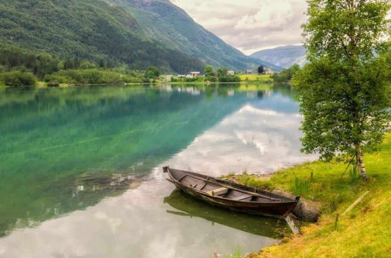 Abandoned wooden boat against shore in turquoise lake, colorful farms in green fields, mountainsides covered in trees