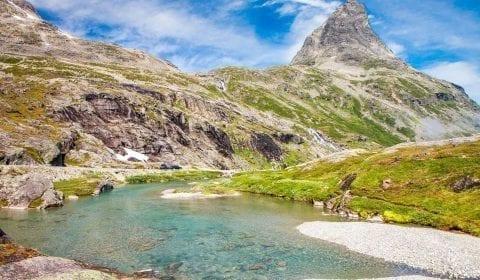 Agua azul clara que fluye en las montañas cercanas a la carretera de los troles en Noruega