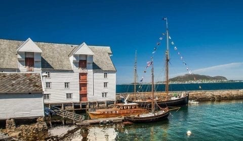 Wooden boats in the water outside the white building of the Fisheries Museum on a clear day, blue sky in Ålesund, Norway