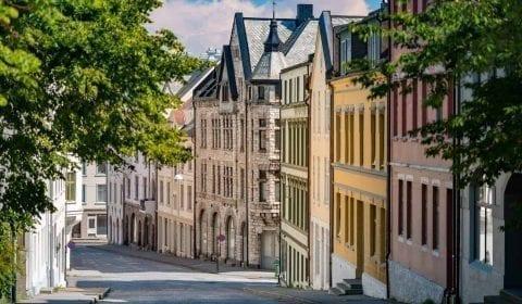 Rolig gate med grønne trær og fargerike Jugendstilhus i sentrum av Ålesund, Norge