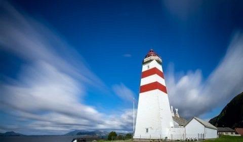 El faro rojo y blanco de Alnes en la isla de Godoy bajo un cielo azul con algunas nubes suaves