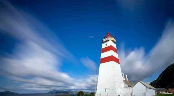 The red and white lighthouse of Alnes on the island of Godoy under a blue sky with a few soft clouds