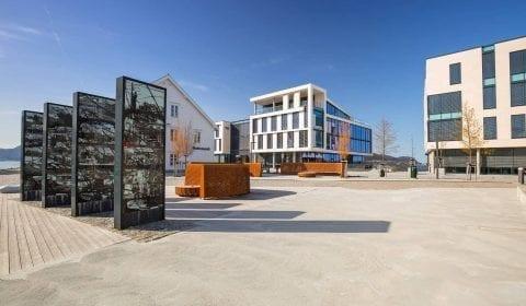 Memorial del incendio de la ciudad en Ålesund en Skansekaia, modernos edificios de oficinas al fondo