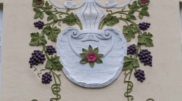 Art nouveau ornament of a vase with grapes on the facade of a house in Ålesund, Norway