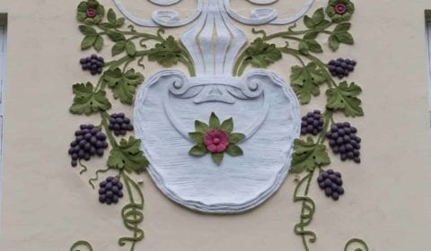 Ornamento Art Nouveau de un florero con uvas en la fachada de una casa en Ålesund, Noruega