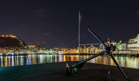 Anchor on a small pier in the city center of Ålesund under the stars late in the evening