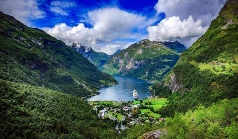 View over UNESCO's Geirangerfjord, one cruise ship in the fjord which is surrounded by steep mountains, from the gorge Flydalsjuvet, Geiranger, Norway