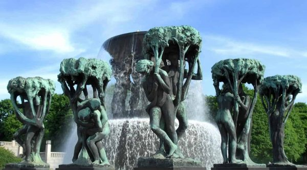 Sculptures of men and woman around a fountain on s clear day in Vigelandsparken, Oslo, Norway