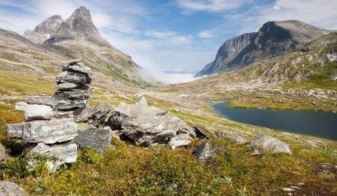 Un mojón en el campo verde al lado de un pequeño lago en las altas montañas cerca del camino del Troll en Noruega