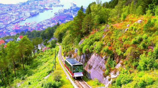 View of the floyen funicular going uphill in Bergen, the city center in the background