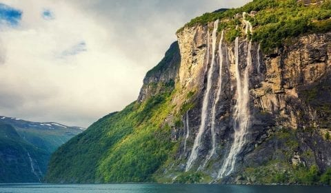 11Seven Sisters Waterfall plunging in the Geirangerfjord, green mountains, cloudy sky