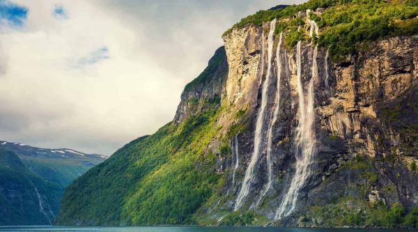 Seven Sisters Waterfall plunging in the Geirangerfjord, green mountains, cloudy sky