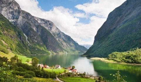 11Green fjord surrounded by high mountains, farms on the shore