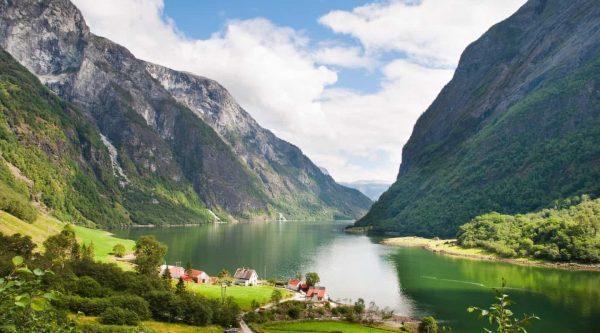 Green fjord surrounded by high mountains, farms on the shore