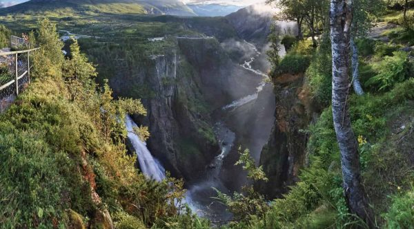 View over the Voringsfossen waterfall tumbling down the mountain in the green Mabodalen valley