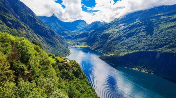 Panoramic view from the Eagle Road viewpoint over UNESCO's Geirangerfjord and the village of Geiranger, Norway