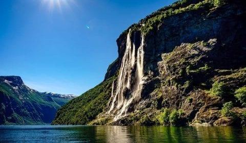 La cascade des Sept Sœurs sous un ciel bleu clair, le soleil brille à Geiranger Norvège