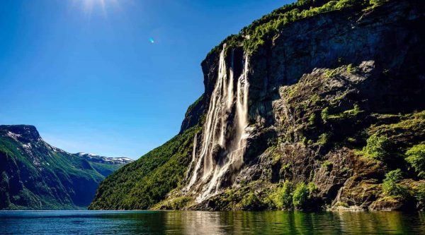 The Seven Sisters waterfall under a clear blue sky, sun shines brightly in Geiranger Norway